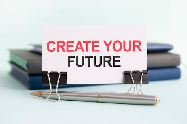 Eine weiße karte mit dem text create your future steht auf einem clip für papiere auf dem tisch vor dem hintergrund von büchern. selektiver fokus