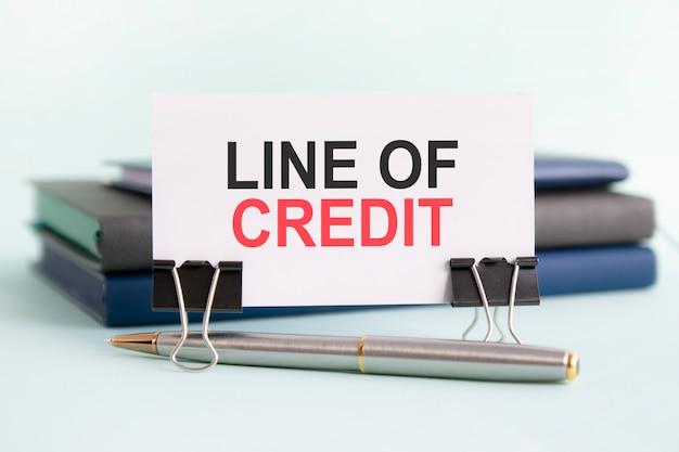 Eine weiße karte mit dem text der kreditlinie steht auf einem clip für papiere auf dem tisch vor dem hintergrund von büchern. selektiver fokus