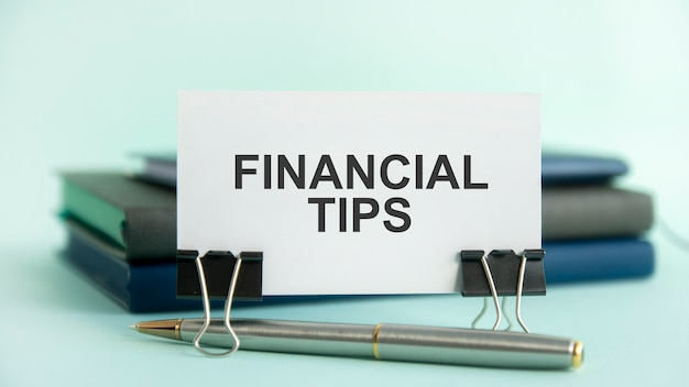 Eine weiße karte mit dem text finanztipps steht auf einem clip für papiere auf dem tisch vor dem hintergrund von büchern. selektiver fokus