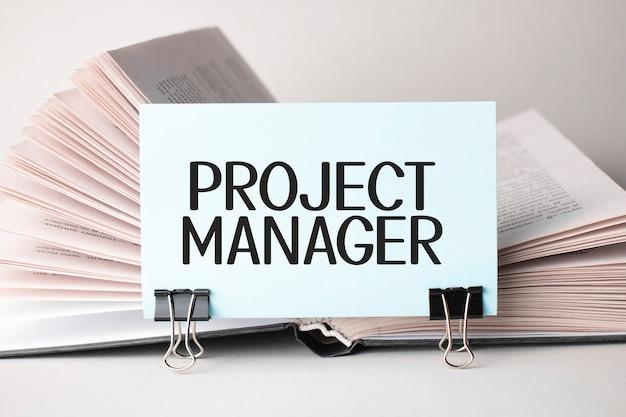 Eine weiße karte mit dem text projektmanager steht auf einem clip für papiere auf dem tisch vor dem hintergrund von büchern. defokussieren