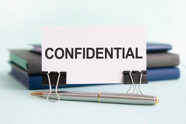 Eine weiße karte mit dem text vertraulich steht auf einem clip für papiere auf dem tisch vor dem hintergrund von büchern. selektiver fokus