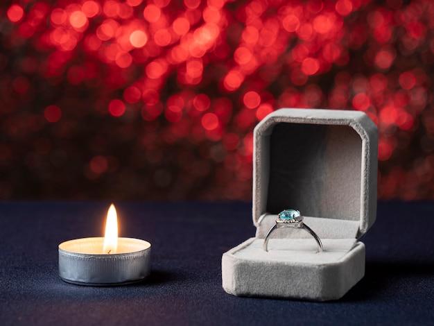 Eine weiße kerze, die brennt und daneben eine schachtel mit einem ring mit einem blauen stein auf einem rosa