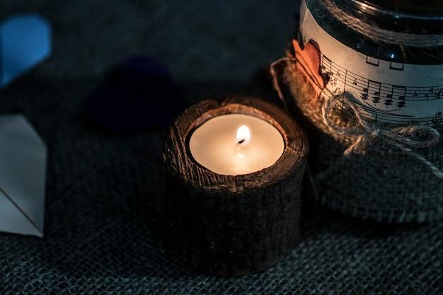 Eine weiße kerze mit dunklem hintergrund - in einem hölzernen kerzenständer.