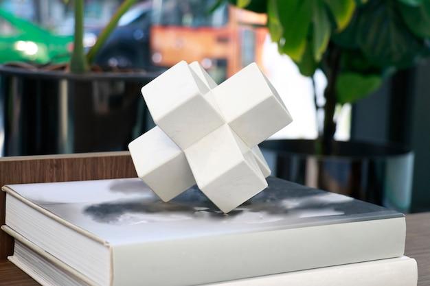 Eine weiße, polygonale keramikform, die zur dekoration auf das buch im wohnzimmer gelegt wird