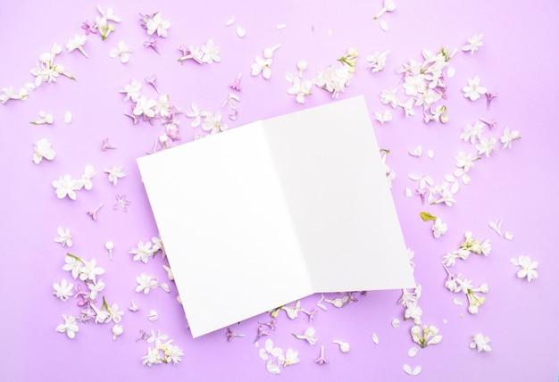 Eine weiße postkarte für text und grüße liegt auf einem hellen hintergrund unter den farben des weißen flieders. von oben betrachten