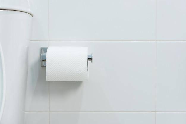 Eine weiße rolle aus weichem toilettenpapier, die ordentlich am chromhalter an einer weißen badezimmerwand hängt. nahansicht