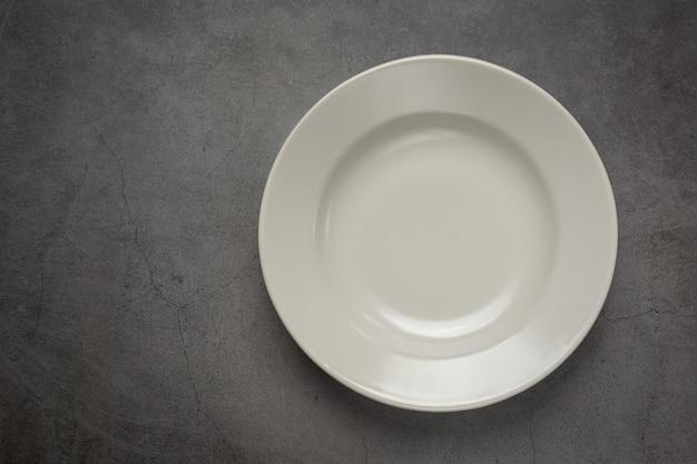 Eine weiße runde leere platte auf dunkler oberfläche