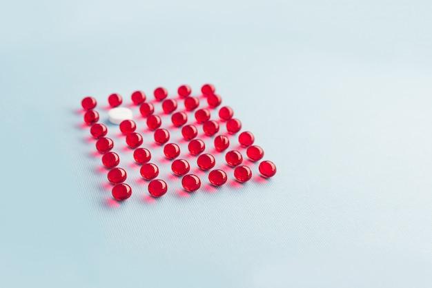 Eine weiße runde tablette in einem gitter aus roten kapseln