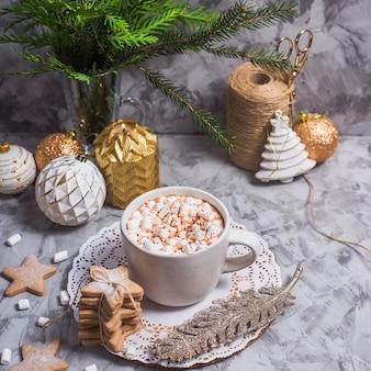 Eine weiße schale mit heißem kakao mit eibisch steht auf einer grauen tabelle