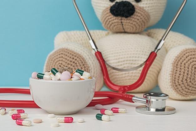 Eine weiße schüssel gefüllt mit medikamenten auf dem hintergrund eines gestrickten bären mit einem stethoskop. das konzept der behandlung von krankheiten.