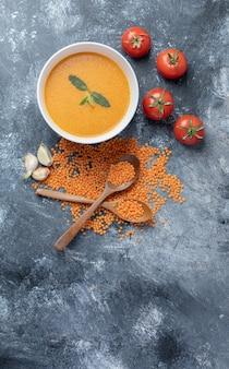 Eine weiße schüssel linsensuppe mit tomaten und holzlöffeln.
