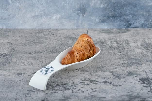 Eine weiße schüssel mit frischen croissants auf einem steintisch.