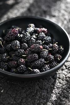 Eine weiße schüssel mit reifen schwarzen maulbeeren sommerfrische maulbeerfrüchte