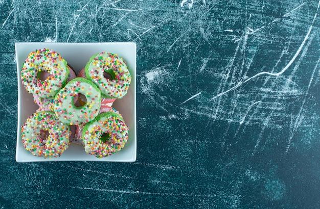 Eine weiße schüssel voll von süßen donuts auf einem blauen hintergrund. hochwertiges foto