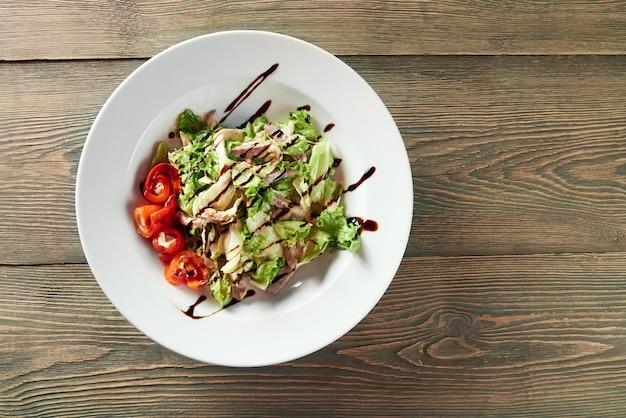 Eine weiße schüssel voller gemüsesalat mit gegrilltem hähnchen, paprika, salatblättern und sauce. sieht delikat und lecker aus.
