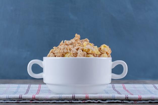 Eine weiße schüssel voller leckerer gesunder cornflakes auf tischdecke.
