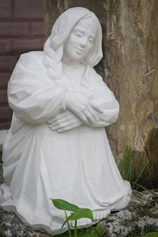 Eine weiße statue eines mädchens in einem alten park.