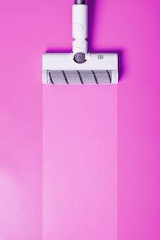 Eine weiße staubsaugerbürste auf rosa hintergrund. das konzept des reinigens oder staubsaugens.