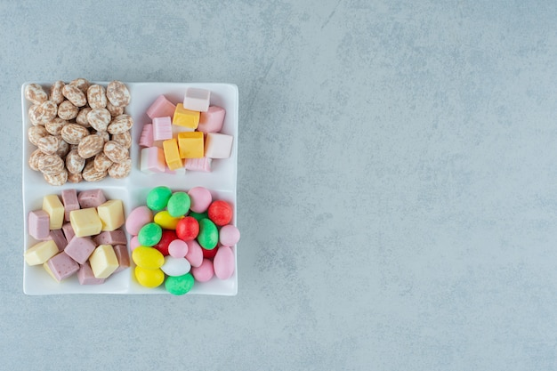 Eine weiße tafel mit marshmallows und bunten bonbons auf weißer oberfläche