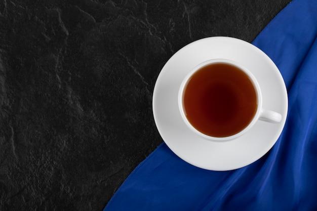 Eine weiße tasse heißen tee auf einem schwarzen tisch.