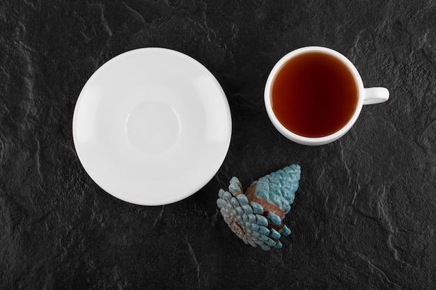 Eine weiße tasse heißen tee mit einem tannenzapfen.