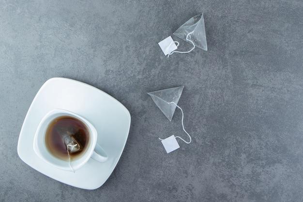 Eine weiße tasse heißen tee mit teebeuteln.