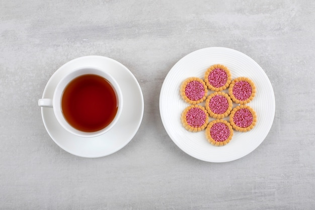 Eine weiße tasse heißen tee und kekse mit streuseln auf einem weißen teller.