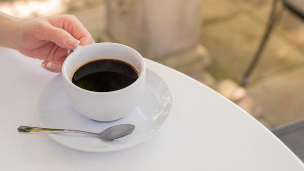 Eine weiße tasse kaffee auf weißem tisch mit arbeitspausenzeit. ein glas heißen espresso.