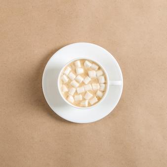 Eine weiße tasse kaffee mit marshmallows gegen das handwerkliche braune papier.