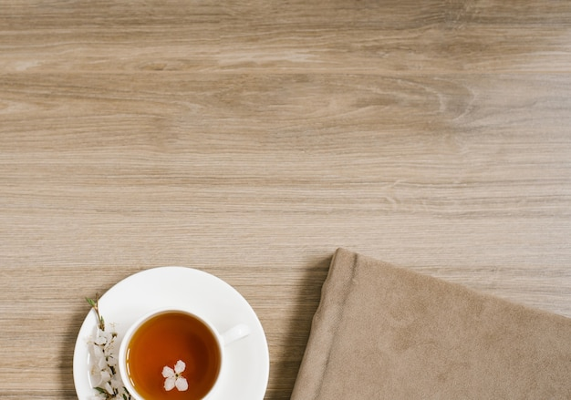 Eine weiße tasse mit schwarzem tee und einem zweig apfelblüte und ein fotoalbum im beigen textileinband
