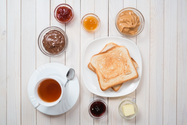 Eine weiße tasse schwarzer tee mit sandwiches oder toasts mit erdnussbutter, schokoladenpaste und erdbeere, johannisbeer- und aprikosengelee oder marmelade auf weißem holztisch, draufsicht, flache lage, frühstückskonzept