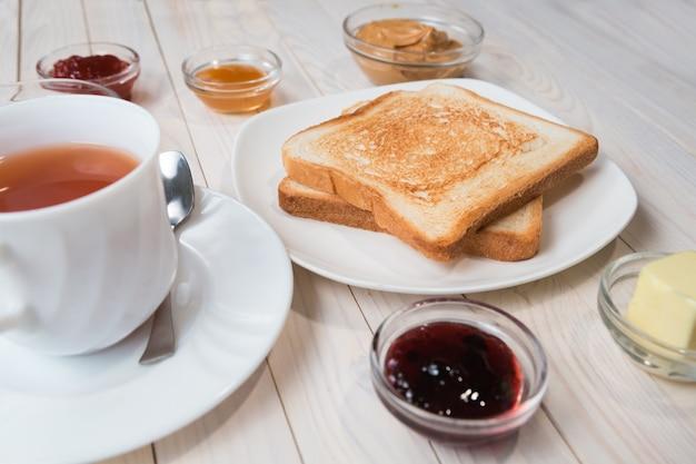 Eine weiße tasse schwarzer tee mit sandwiches oder toasts mit erdnussbutter, schokoladenpaste und erdbeere, johannisbeer- und aprikosengelee oder marmelade auf weißem holztisch, nahaufnahme, frühstückskonzept