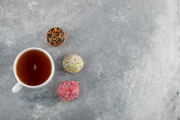 Eine weiße tasse tee mit kleinen leckeren donuts.