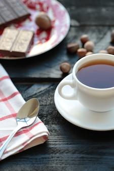 Eine weiße tasse tee mit schokoriegel auf dem holztisch.