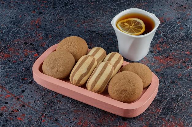Eine weiße tasse tee mit süßen frischen keksen in einem rosa brett auf einer dunkelheit
