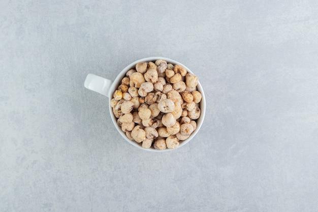 Eine weiße tiefe tasse voller köstlicher runder speisen.