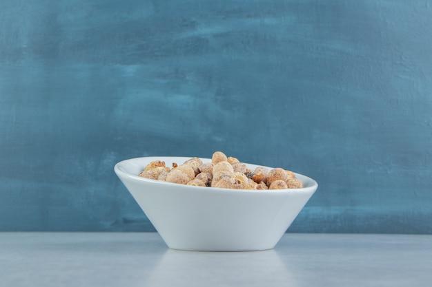 Eine weiße tiefe tasse voller köstlicher trockenfrüchte.
