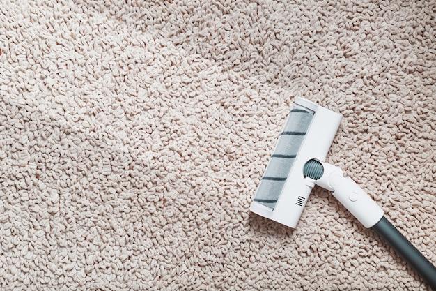 Eine weiße turbobürste eines akku-staubsaugers auf dem teppich. indoor mit einem sauberen streifen