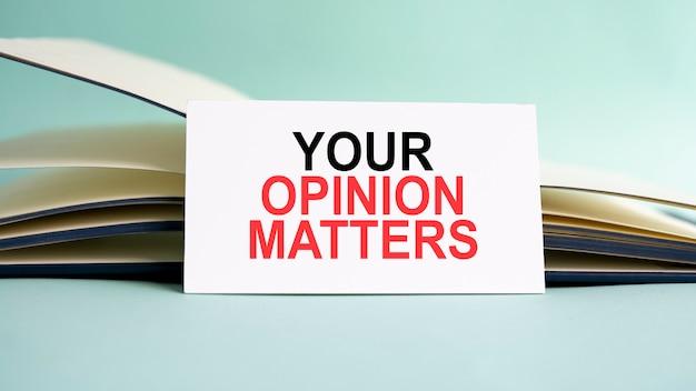 Eine weiße visitenkarte mit dem text your opinion matters steht auf einem schreibtisch vor dem hintergrund eines offenen tagebuchs. unkonzentriert.