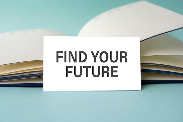 Eine weiße visitenkarte mit find your future text steht auf einem schreibtisch vor dem hintergrund eines offenen tagebuchs. unkonzentriert.