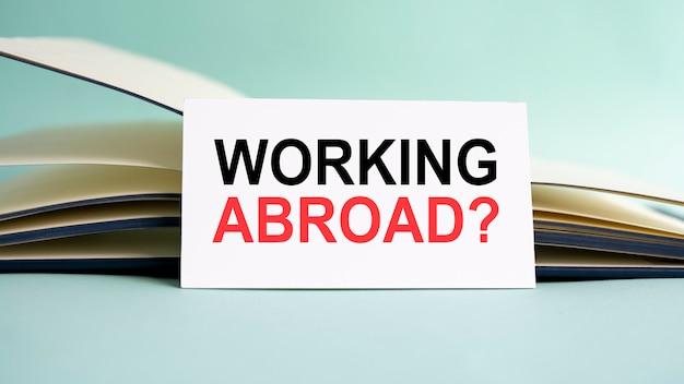 Eine weiße visitenkarte mit work abroad text steht auf einem schreibtisch vor dem hintergrund eines offenen tagebuchs. unfokussiert