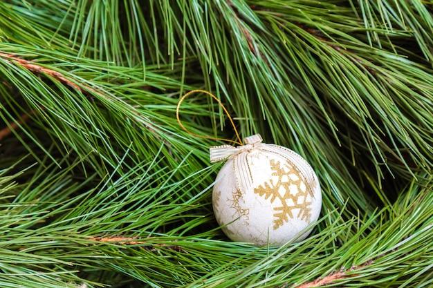 Eine weiße weihnachtskugel auf einem weihnachtsbaum