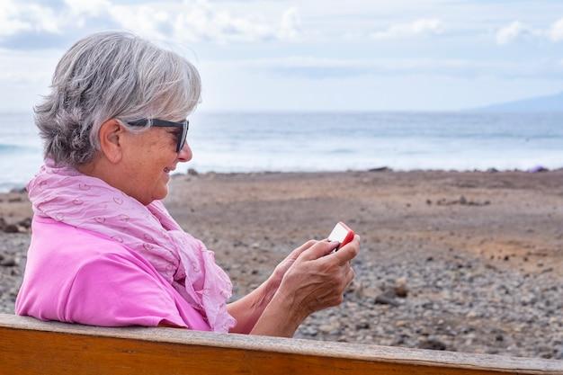 Eine weißhaarige ältere frau in rosa kleid mit sonnenbrille mit smartphone. sitzen auf einer bank am strand mit meer und wellen im hintergrund. alte rentner modern und technisch