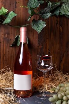 Eine weißweinflasche weißwein der vorderansicht zusammen mit grünen trauben und grünen blättern, die auf dem grauen schreibtischalkohol-weingutgetränk isoliert werden