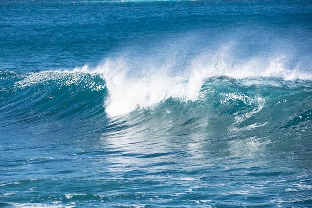 Eine welle, die den blauen atlantik einläuft.