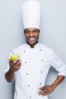 Eine wichtige zutat für obstsalat. selbstbewusster junger afrikanischer koch in weißer uniform
