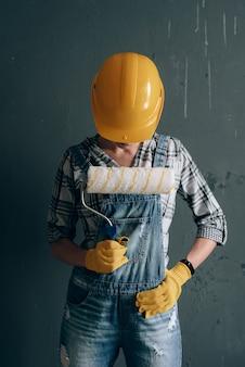 Eine willensstarke frau in einem bauhelm, fäustlingen, einer schutzbrille und einem overall ist zu hause mit reparatur- und bauarbeiten beschäftigt. konzept einer starken und unabhängigen frau