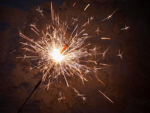 Eine wunderkerze brennt mit hellen funken in einem dunklen raum