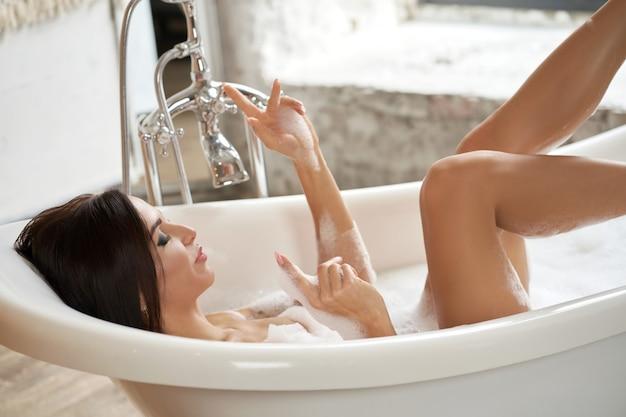 Eine wunderschöne frau amüsiert sich in einer weißen badewanne in einem hellen raum mit einem großen fenster.