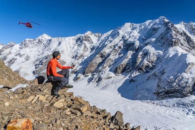 Eine wunderschöne landschaft mit bergen, einem riesigen blauen gletscher und einem bergsteiger mittleren alters, der mit einem walkie-talkie in der hand sitzt, ruft den rettungsdienst, der auf einen rettungshubschrauber wartet